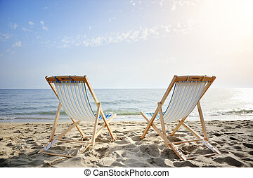 couple of chairs on sandy beach at sunset looking for the...