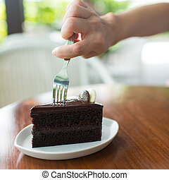 Close-up of a hand holding a fork about to slice into a...