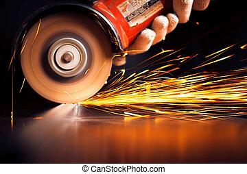 Worker cutting metal with grinder. Sparks while grinding...