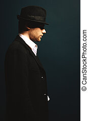 The man in style Chicago gangster with gun on dark...