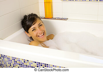 Laughing in bath tub full of foamF - Cute fresh girl smiling...