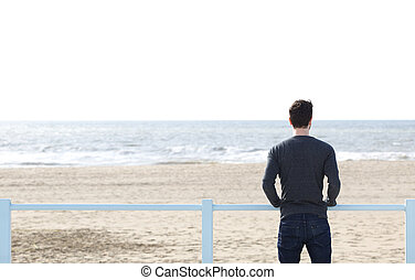 Man standing alone looking at sea - Portrait of a young man...