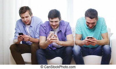 smiling friends with smartphones at home - friendship,...
