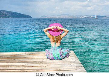 Woman sitting at the beach - Beautiful woman with hat...