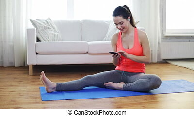 smiling teenage girl stretching on mat at home - fitness,...