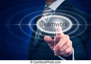 Teamwork - A businessman Pointing towards a teamwork button,...