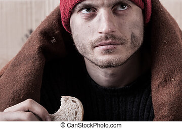 Homeless man eating a piece of bread - Homeless and hungry...