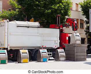 Recycling truck picking up bin at city street. Spain