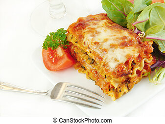 Lasagna on a Plate with Salad - Lasagna and salad on a white...