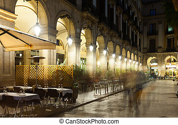 night view of Placa Reial with restaurants in Barcelona -...