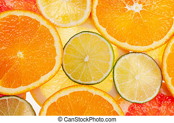 background of different colored slices of citrus fruits...