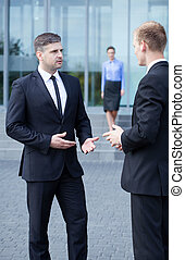 Conversation in front of business centre, vertical