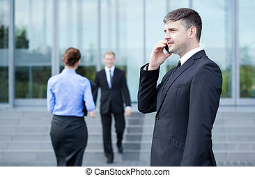 Man in front of business centre - Man talking on phone in...