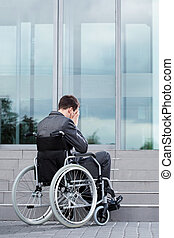 Stressful man on wheelchair before work in business centre