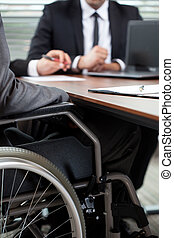 Man on wheelchair during conversation with boss