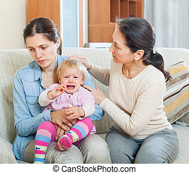 woman comforting  adult daughter with toddler