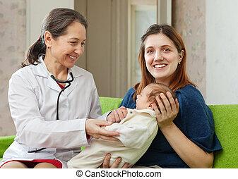 children's doctor examining newborn baby - friendly mature...