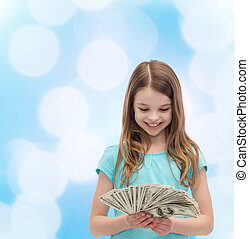 smiling little girl looking at dollar cash money - money,...