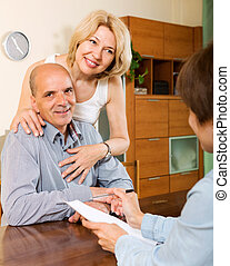 Mature couple with insurance agent - Positive elderly couple...