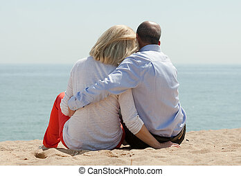 Mature lovers sitting on beach - Mature lovers sitting on...