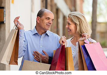 Aged couple with purchases - Smiling elderly couple going by...