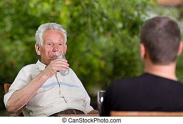 Relaxing in garden - Old man drinking water in garden while...