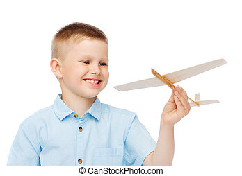 smiling little boy holding a wooden airplane model - dreams,...