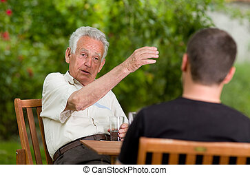 Chatting in garden - Serious old man talking with grandson...