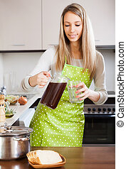 Blonde woman pouring  kvass in glas