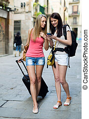 Two european students on vacation with luggage and using the...
