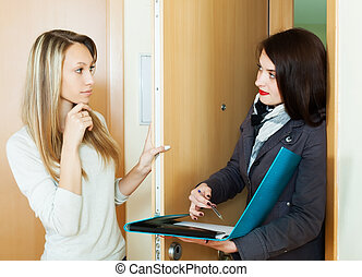 Girl conducting survey among residents in door at home