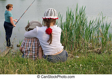 Children rest in nature on the lake in summer