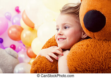 Portrait of sweet little girl hugging teddy bear, close-up