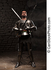 Medieval Knight posing with two swords on in a dark stone...