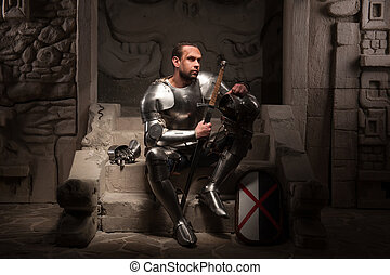 Medieval knight sitting on the steps of ancient temple -...