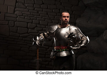 Medieval Knight posing with sword in a dark stone...