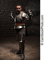Medieval Knight posing with sword in a dark stone background...