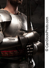 Closeup portrait of medieval knight in armor holding a sword...