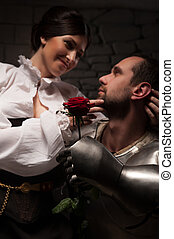 Knight giving a rose to lady - Closeup portrait of medieval...