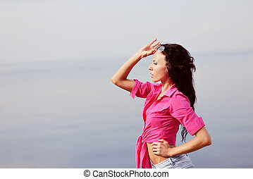 young brunette wearing pink shirt by the sea