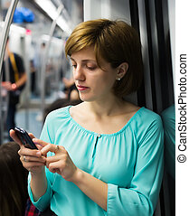 Female passanger calling by mobile in train