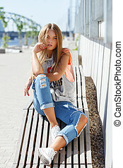 Beautiful girl in torn jeans - Outdoor, street. Attractive...
