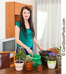 Female gardener with flowering plants in pots at home