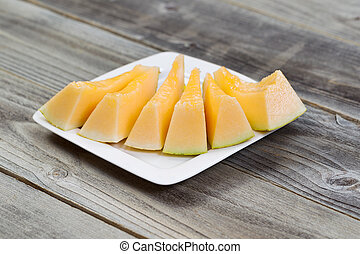 Fresh Melon Slices on White Plate with rustic wood...