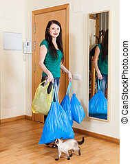 woman near door with garbage - brunette woman near door with...
