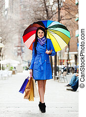 woman in blue with shopping bags and umbrella