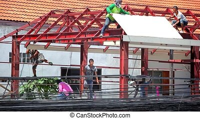 THAILAND, KOH SAMUI, JULY 2, 2014: Construction crew working on the roof sheeting of house at background Of many electric cables. Video