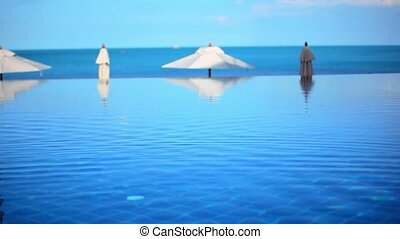 Swimming pool by the sea on background of blue sky near beach and white umbrellas. Video shift motion Koh Samui Thailand