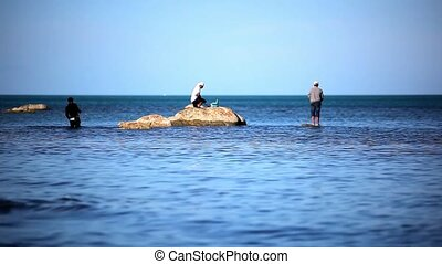 Fishermans at the sea standing on stones go fishing Video...