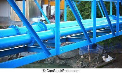 Industrial blue pipelines next to bridge above river Video...